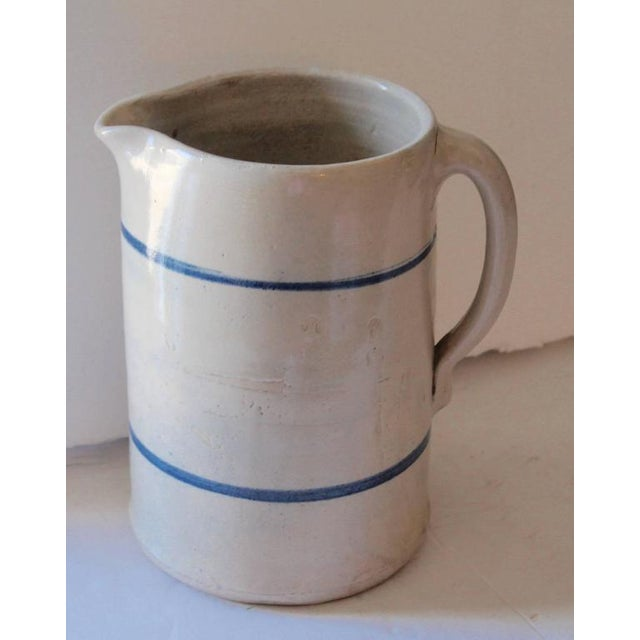 What a great looking country pitcher. This is a handmade and painted stoneware pitcher. With two simple lines in blue. The...