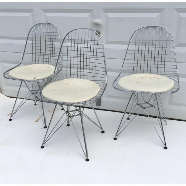 This set of three vintage wire dining chairs features Eames style Eiffel pyramid bases with single seat pads for added...