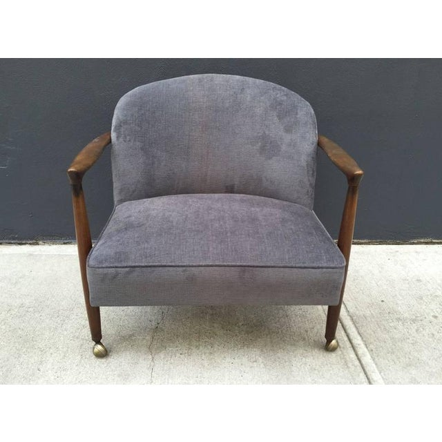 Pair of sculptural Ib Kofod-Larsen lounge chairs. Casters to the front legs. Walnut sculptural frame. Newly upholstered in...