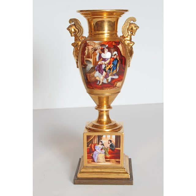 A pair of French porcelain urns, gilt overall with Pegasus busts on sides. Painted panels on side and base with painted...