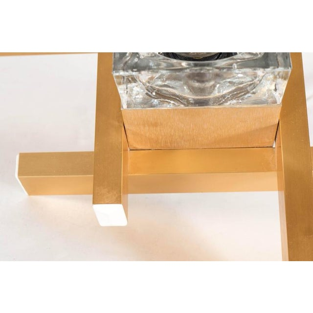 A Mid-Century Modernist flush mount brushed brass fixture by Sciolari. A glass cube surrounded by brass bands forming a...