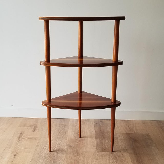 A beautiful Mid-Century Modern corner three-tiered shelf made in Italy. There is a nice detail of inlaid bronze on each...