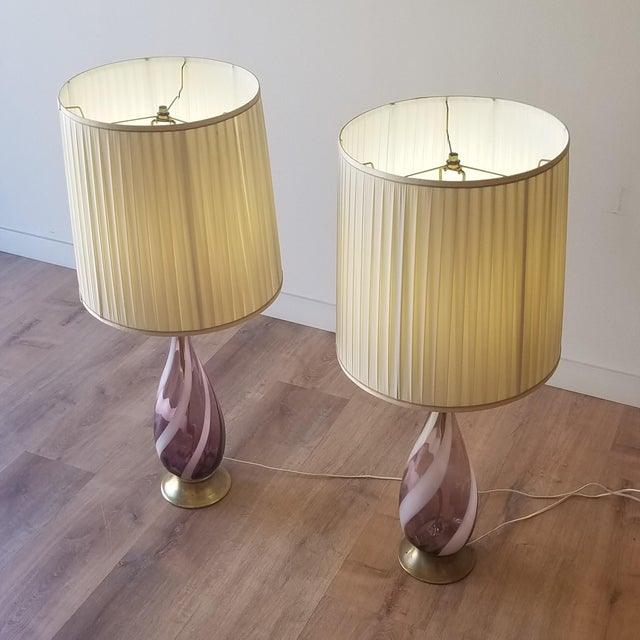 A beautiful pair of Italian amethyst Murano glass table lamps with white swirls. The brass bases and finials have signs of...