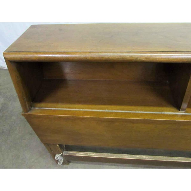This is a solid wood, golden oak stained queen sized headboard. This headboard has a great section for storing items....