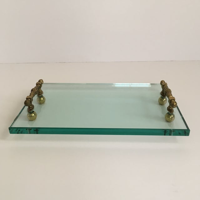 Thick beveled glass with stylish brass handles and feet. Made in the style of Hollywood Regency in the late 20th century.
