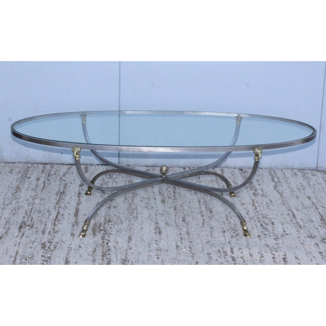1960s modern steel frame with brass ram's head and feet oval coffee table.