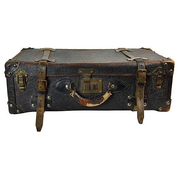 Worn leather European suitcase with decorative lining. No maker's mark.