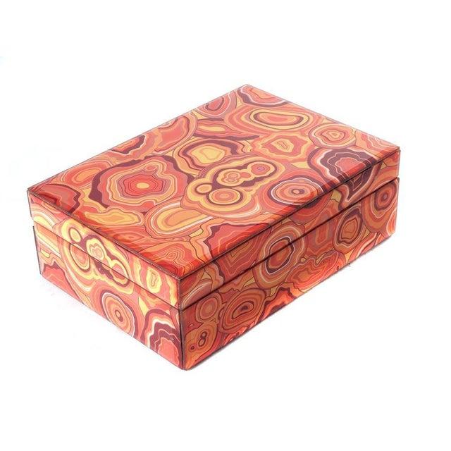 A decorative lidded box featuring an orange malachite pattern.