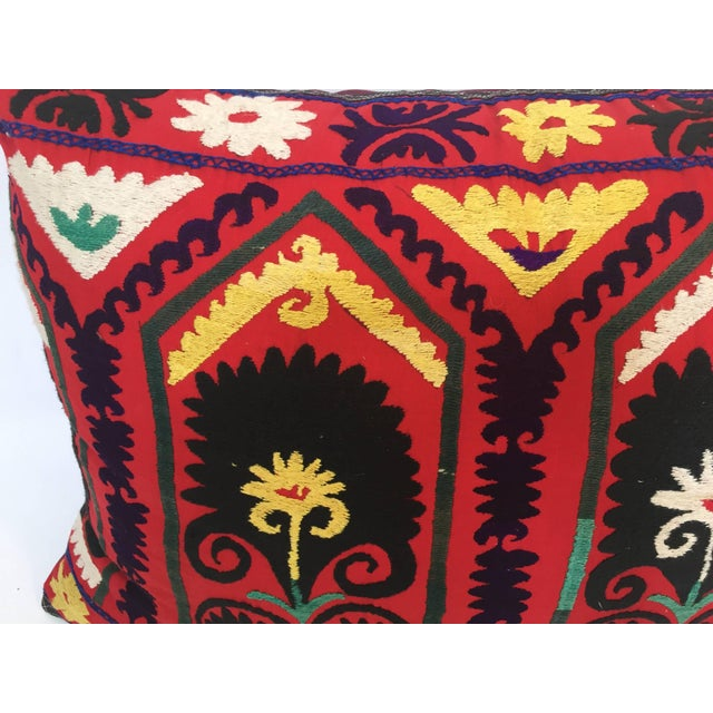 Large vintage colorful Suzani embroidery throw pillow red embroidered with colorful threads. A reddish embroidered pillow...