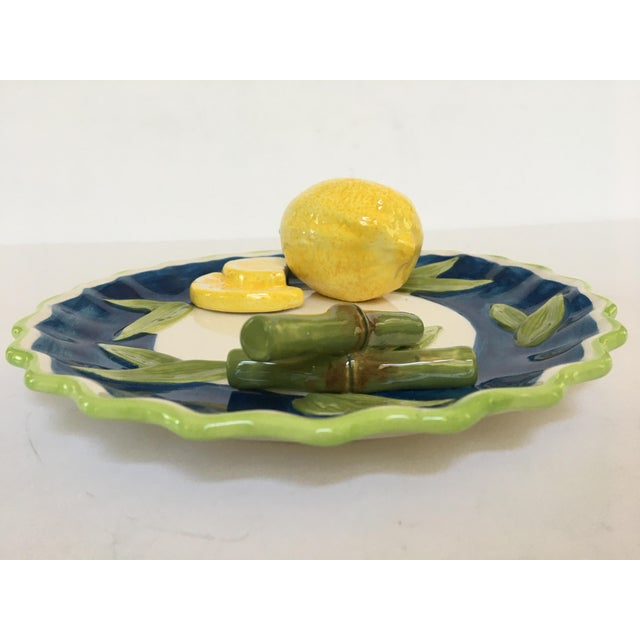 Offering a decorative, Trompe l'Oeil painted, scalloped plate. Adorning this realistic piece is a whole yellow lemon, two...
