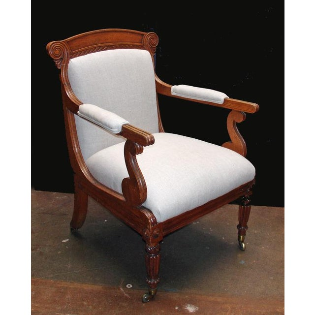 An elegant, simply carved oak open arm library chair with a generous seating depth. The front legs are cylindrical and...