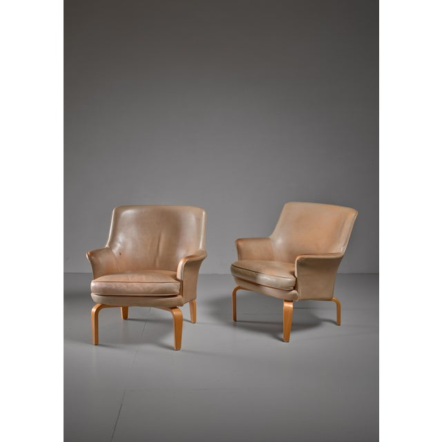 A pair of beige leather 'Pilot' lounge chairs on birch feet by Arne Norell for Norell Mobel AB. Labeled by Norell and in a...