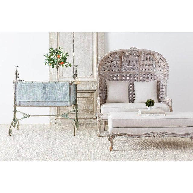 Fabulous French Louis XV style hooded balloon settee or porter's settee with ottoman. Featuring a hooded canopy top in the...