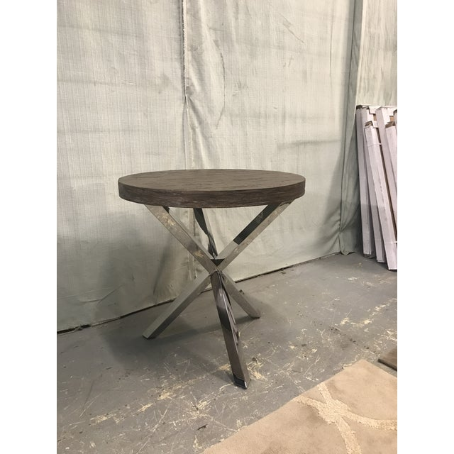 This gorgeous chairside table combines a wood top with a polished stainless steel base in a grey pearl finish, giving it a...