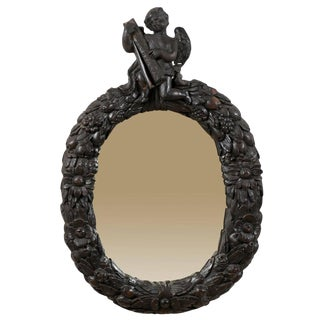 An 18th Century English Oval Richly Carved Deep Brown Colored Wood Wall Mirror For Sale