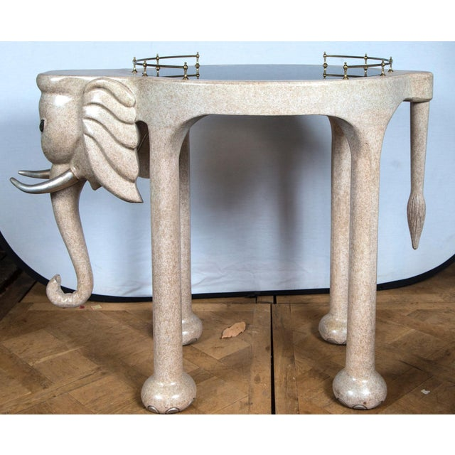 Marge Carson elephant rolling bar cart or table. Made of composition wood with a tinted glass top and brass rails.