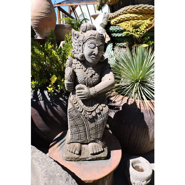 A rustic, outdoor carved stone statue from Batubalan, Bali.