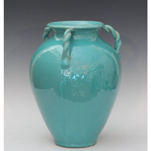"Large royal crown vase in turquoise glaze with three rope twist handles, circa 1940. Measures: 13 1/2"" high, 12"" diameter...."