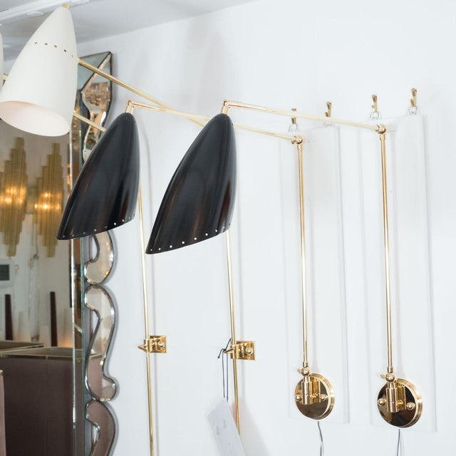 Pair of articulated brass sconces with enameled metal shades. Measured as shown. Origin: Italy Circa: 1960 Dimensions:...