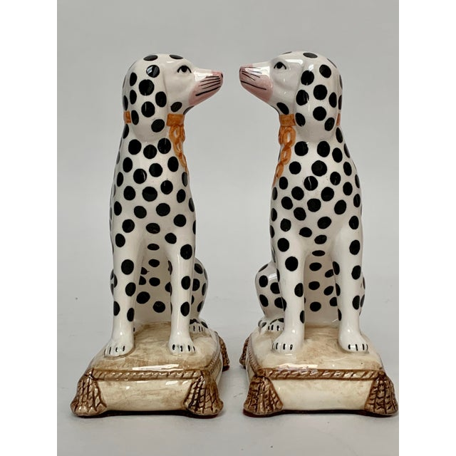 Two porcelain Staffordshire style Dalmatians hand decorated with golden leashes and bases shaped like tasseled cushions...