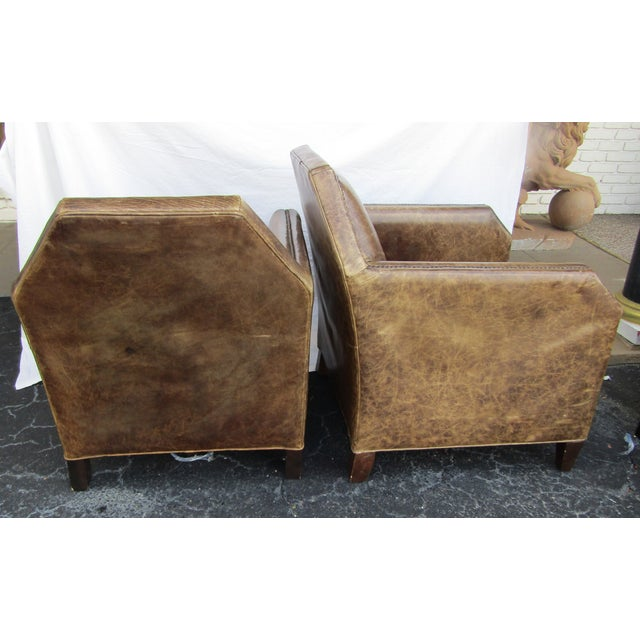 Pair of leather accent chairs with a unique design. The chairs are covered in light brown distressed leather, down filled...