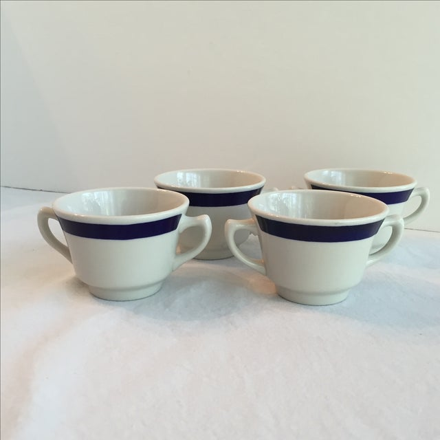 Four stoneware bouillon soup cups with two handles. White trimmed with a cobalt blue band. Made in the USA.