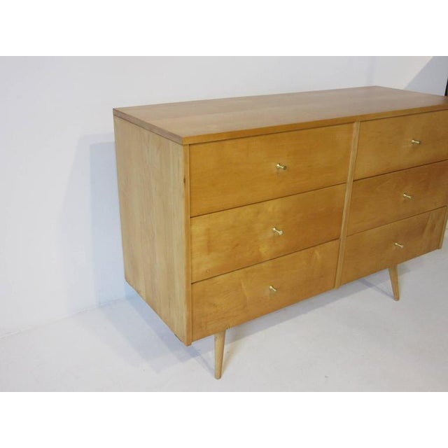 A McCobb solid maple six-drawer dresser chest in a honey toned finish with brass Tee pulls sitting on matching conical...