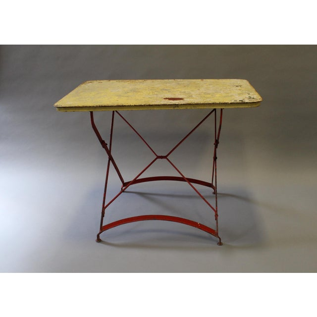 Metal industrial bistro table with red legs and a painted yellow top splattered with red and green paint. The yellow paint...