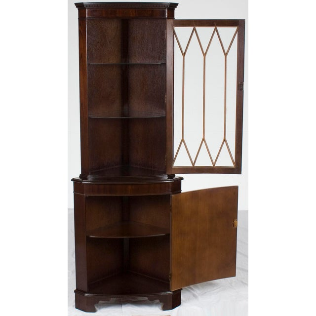 Crafted around the year 1960, this antique mahogany corner cabinet is an exemplary piece of quality English craftsmanship....