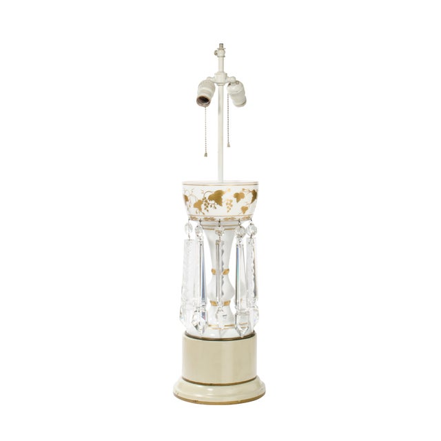 The white glass and gold painted vessel body is elevated on a cream colored enameled base. There are 10 cut crystal drop...
