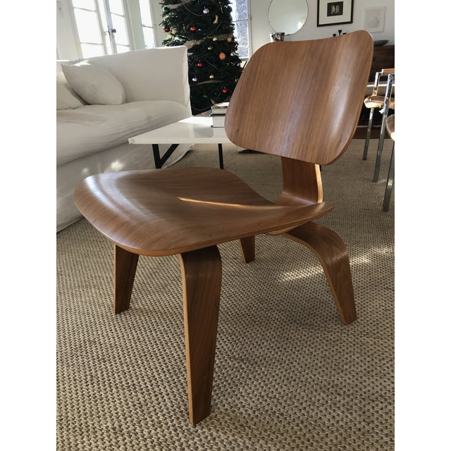 Gently-used Eames LCW in walnut with Herman Miller certificate of authenticity (photo included). Minor signs of wear; in...