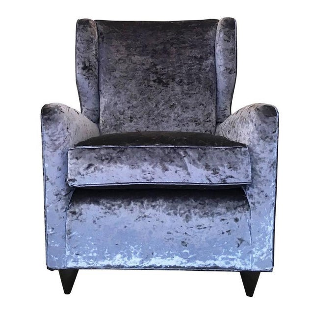 Beautifully designed pair of Italian Mid-Century armchairs with wings and wood feet. One has been re-upholstered with the...