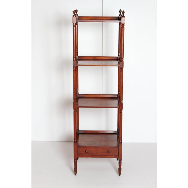 An English Georgian four-tier whatnot with a drawer. The slender turned and baluster shaped supports terminating with urn...