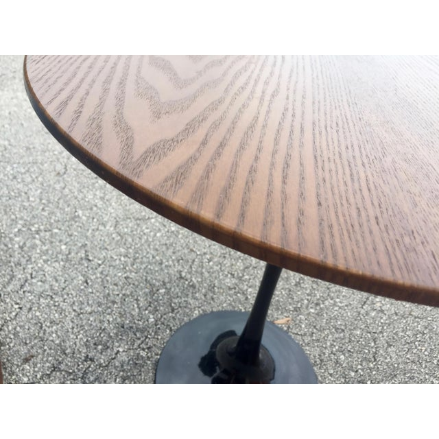 A Knoll style tulip table. This pieces includes a heavy metal base and a walnut top. It is in excellent condition. No...