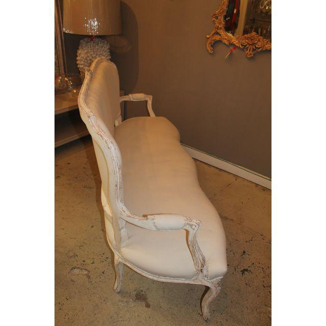Louis XV-style settee that has been reupholstered in muslin. This settee has beautiful primrose carvings between the...