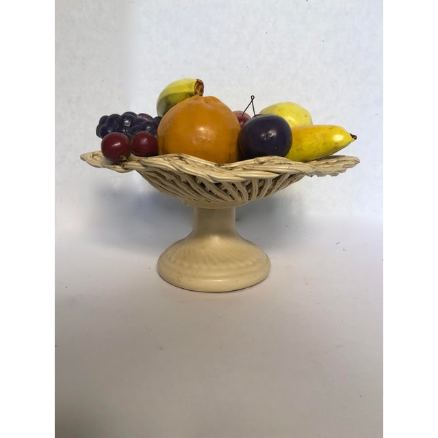 A beautiful arrangement of fruit is displayed in footed cream round, lattice work basket. The fruit arrangement includes...