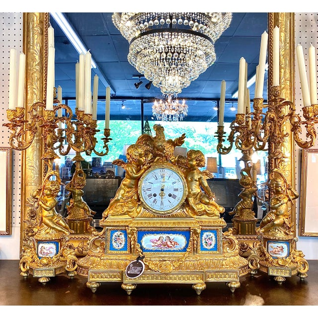 French Louis XVI Garniture mantle set by Villard, Paris. Clock constructed in gilt bronze, and dressed with Bleu Celeste...