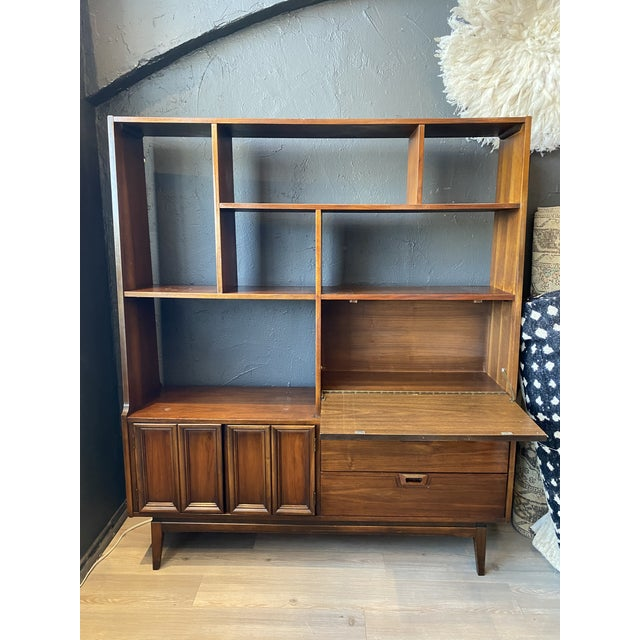 Mid-Century Modern walnut shelving unit with cabinets and pull down desk. Beautiful and original condition. Equipped with...