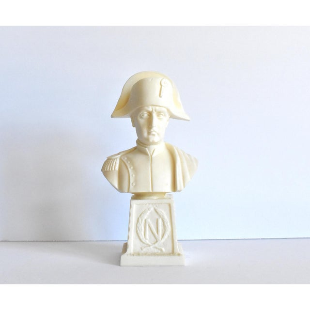 """A vintage off-white resin bust of Napoleon atop a pedestal with the Napoleonic """"N"""" in a laurel wreath. """"I. Giusti"""" on the..."""