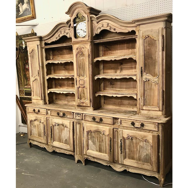 French Provincial vasselier in walnut with built in clock, weights, and pendulum. Consists of shelves, cupboards, doors,...
