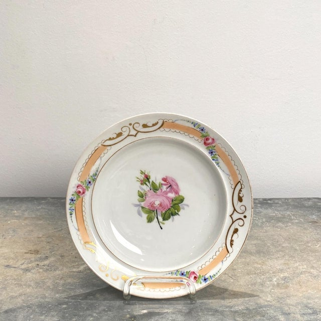 A set of 8 French Paris Porcelain soup bowls with a floral center and border and peach band around the rim