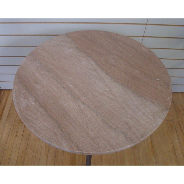Exceptionally versatile round stone top table with a hefty cast iron three-leg base. Stone is variegated pinks, whites and...