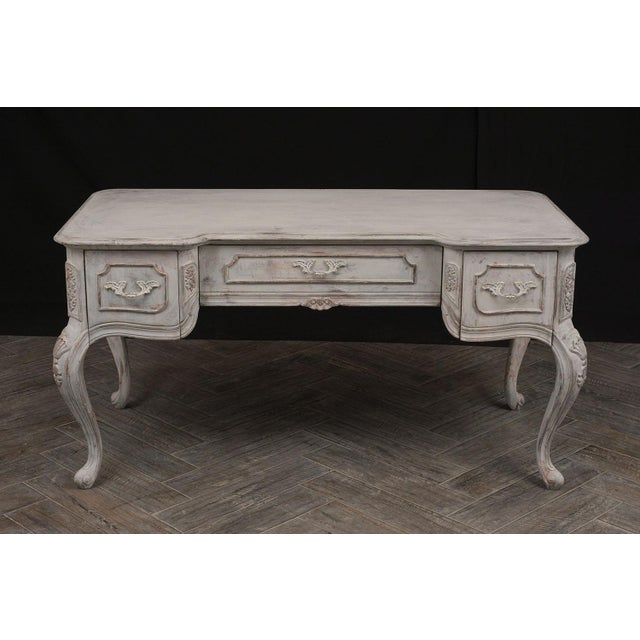 This is a 1980's French Desk in Louis XV-style. Desk has a solid beveled wooden top. Followed by 3 front drawers with...