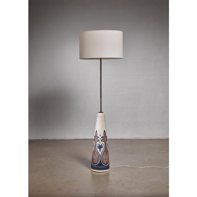 A ceramic floor lamp with a long brass stem and a blue and brown, designed by Rigmor Nielsen for Søholm. The measurements...