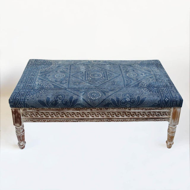 Indigo dot vintage fabric covered ottoman with carved wood white wash trim frame and legs.