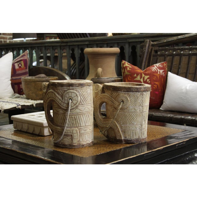 Made from bleached teak wood, this vintage bucket was originally used to transport water and is designed with a tribal motif.