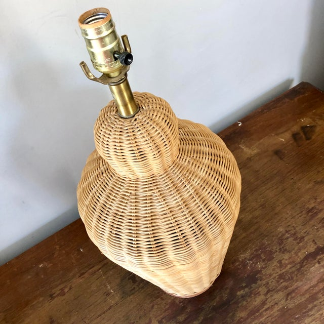 A natural wicker table lamp on wood base.