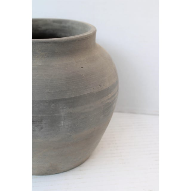 Antique handcrafted matte gray clay pot with hand-thrown details, handles, and time-worn patina.
