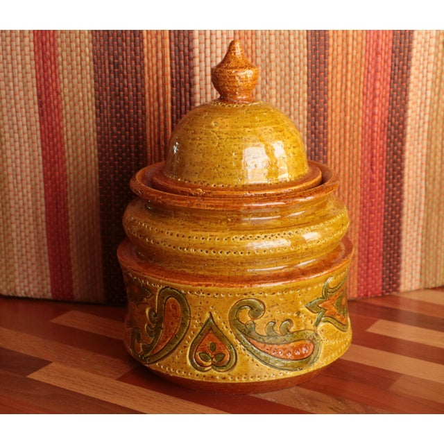 A sunny yellow, orange, and green paisley covers this lidded pottery jar hailing from the 1960s. Designed by Aldo Londi...