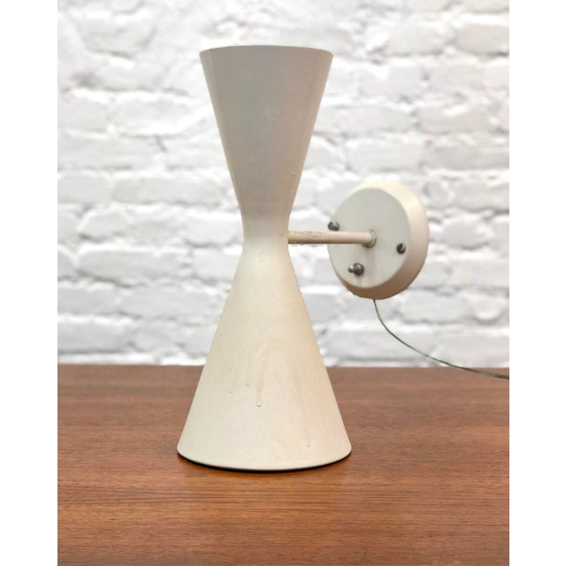 """Classic diablo """"hourglass"""" MCM Wall sconce with up and down light. The piece is from the mid 20th century."""
